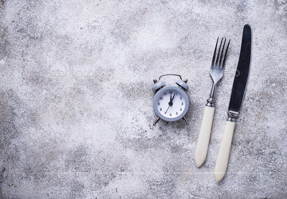 Grey alarm clock with knife and fork - Stock Photo - Images