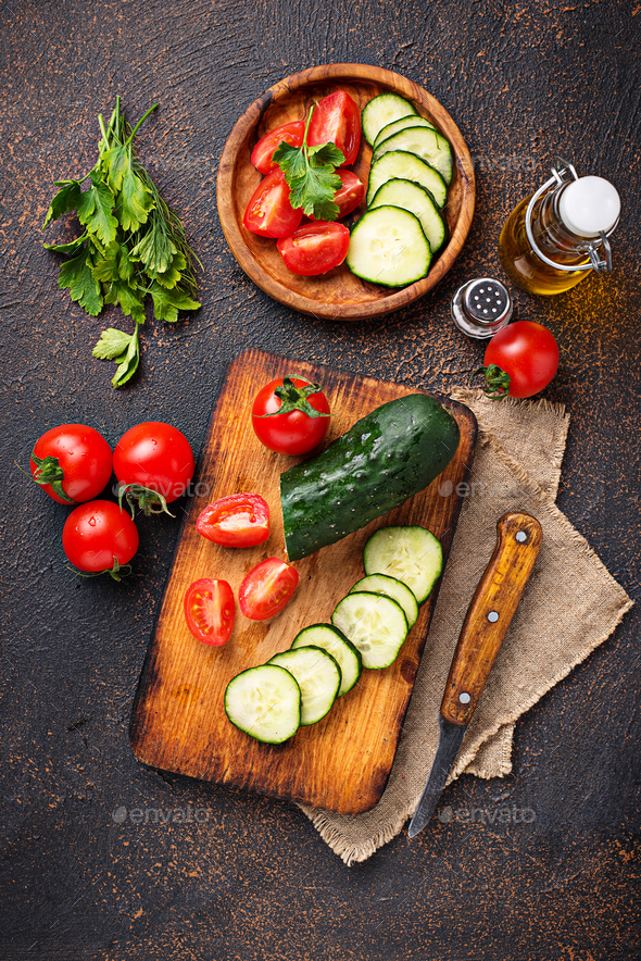 Sliced tomato and cucumber on cutting board - Stock Photo - Images