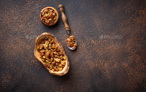 Raisins in wooden bowl on rusty background - Stock Photo - Images