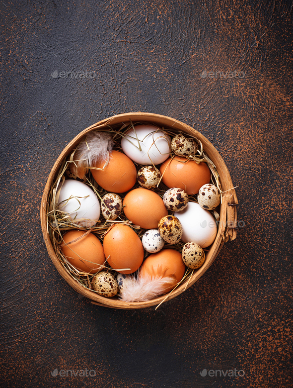 Fresh raw chicken and quail eggs in sieve - Stock Photo - Images
