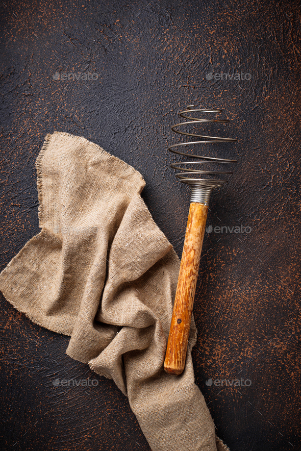 Vintage wooden whisk on old rusty background - Stock Photo - Images