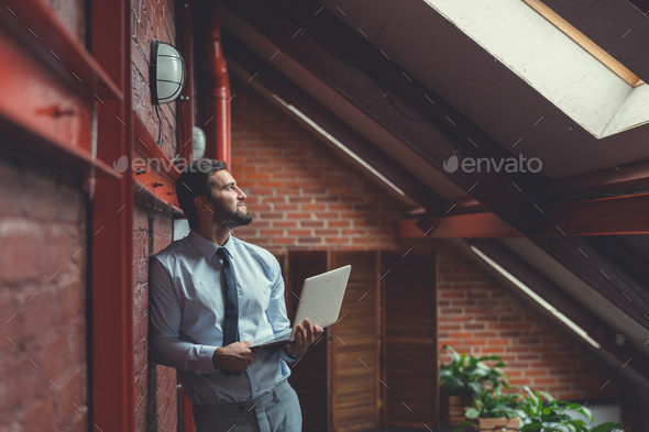 Young businessman with a laptop in the loft - Stock Photo - Images