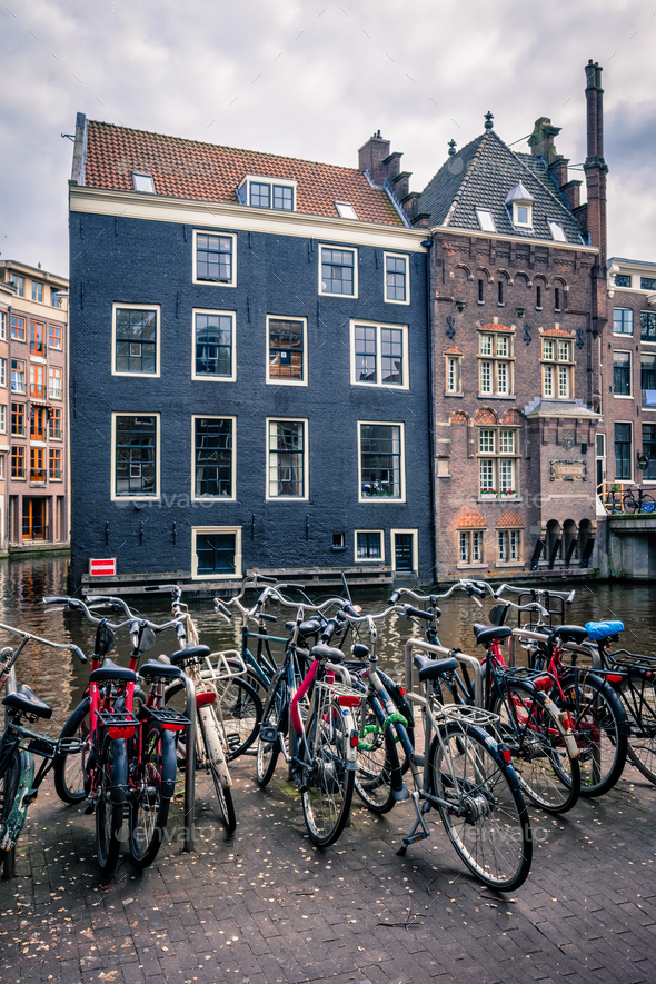 Bicycles in Amsterdam street near canal with old houses - Stock Photo - Images