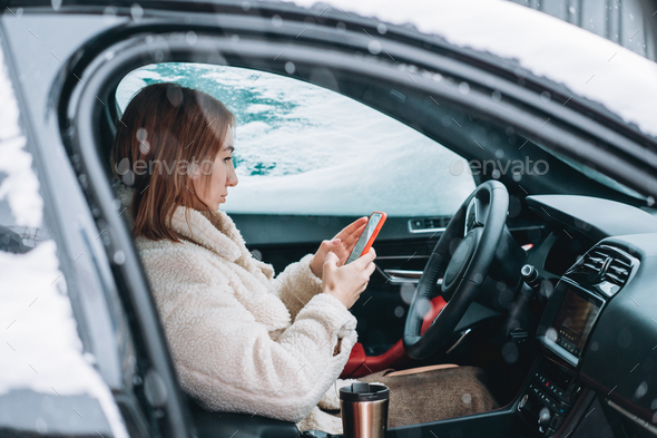 Attractive woman driver nsitting behind the steering wheel in her car - Stock Photo - Images