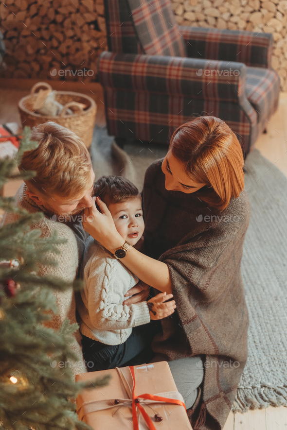 Young caucasian family mom dad son near fireplace christmas tree - Stock Photo - Images