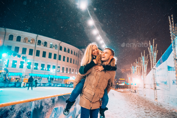 Cheerful and playful couple in warm winter outfits are fooling around - Stock Photo - Images