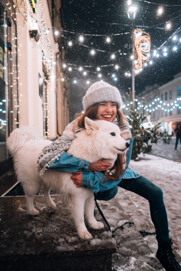 A woman is hugging her dog on a night street - Stock Photo - Images