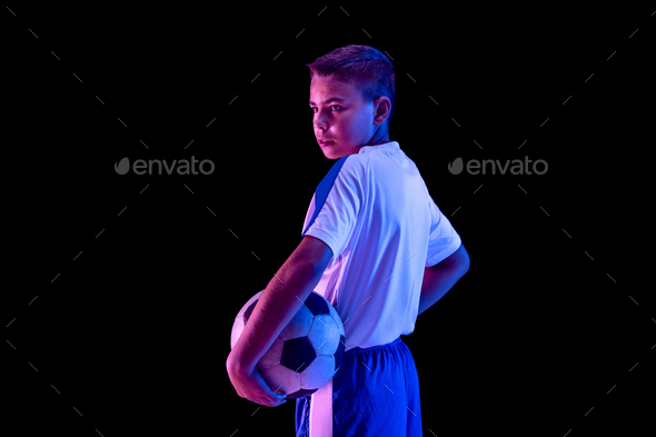 Young boy as a soccer or football player on dark studio background - Stock Photo - Images