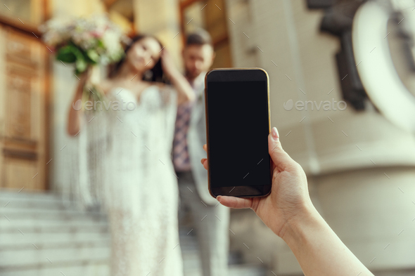 Caucasian romantic young bride celebrating his marriage in city - Stock Photo - Images