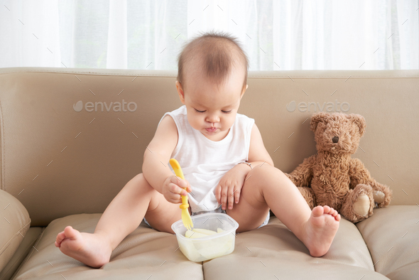 Little girl eating pear - Stock Photo - Images