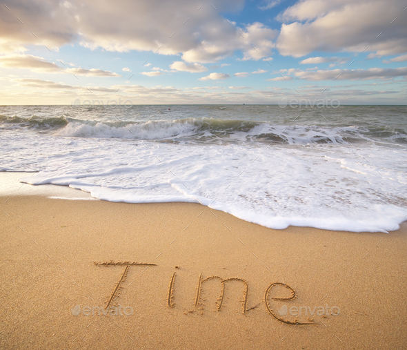 Time word on the sea sand. - Stock Photo - Images