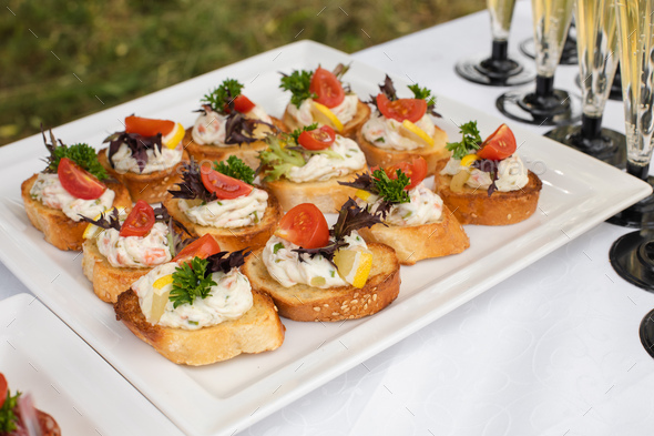 Delicious canape with sausage and tomato.Canapes on white ceramic plates at wedding reception - Stock Photo - Images
