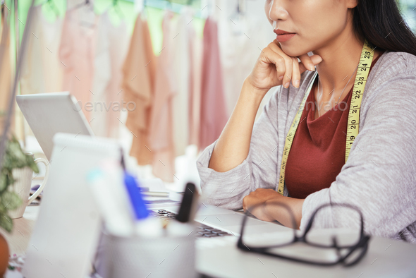 Crop tailor using laptop and thinking - Stock Photo - Images