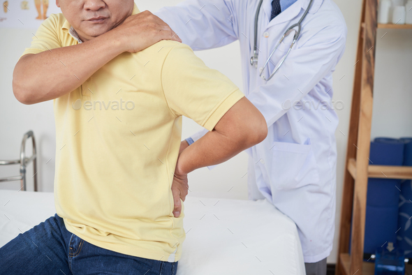 Anonymous doctor examining injured patient - Stock Photo - Images