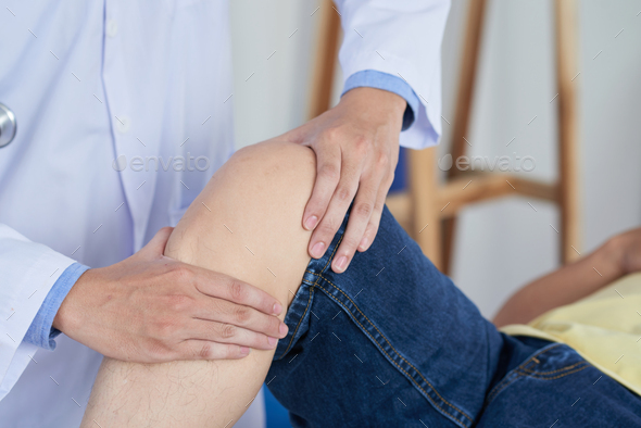Anonymous doctor massaging knee of patient - Stock Photo - Images