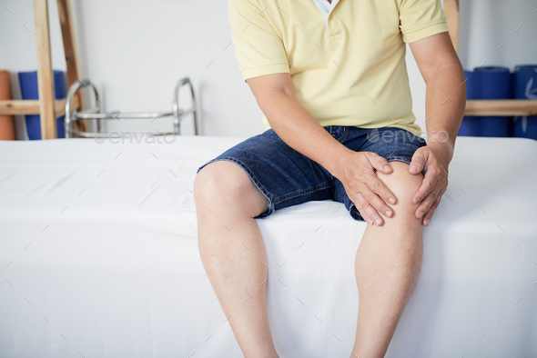 Crop man touching aching knee - Stock Photo - Images