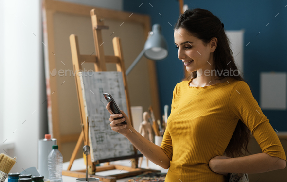 Artist working in the studio and chatting with her phone - Stock Photo - Images