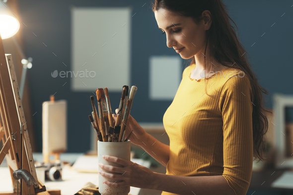Woman choosing the brushes for her artwork - Stock Photo - Images