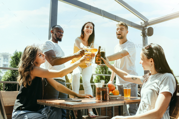 Young group of friends drinking beer and celebrating together - Stock Photo - Images