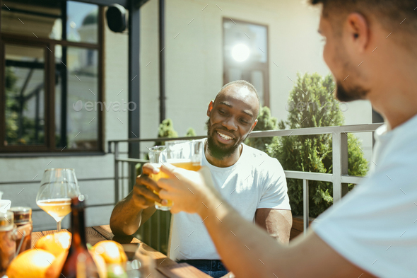 Young men drinking beer and celebrating together - Stock Photo - Images