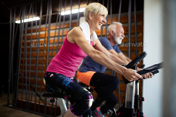 Happy senior people doing indoor biking in a fitness club - Stock Photo - Images