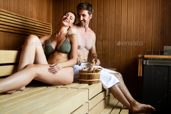 Beautiful young couple sitting together in a sauna - Stock Photo - Images