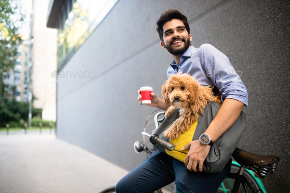Young man drinking coffee while sitting on his bicycle with dog outdoors - Stock Photo - Images
