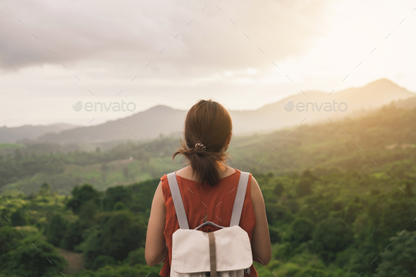 Young woman traveler looking at sunset over the mountain - Stock Photo - Images
