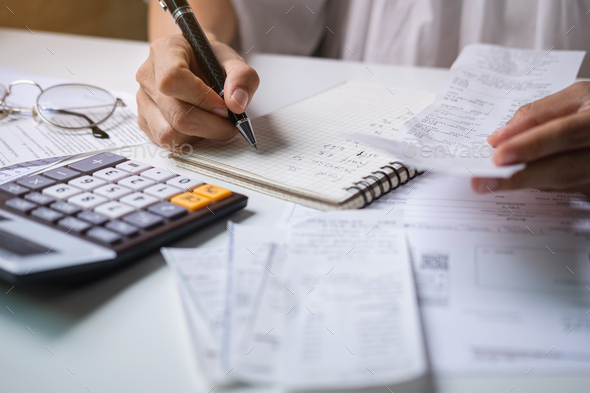young woman checking bills, taxes, bank account balance and calculating expenses - Stock Photo - Images