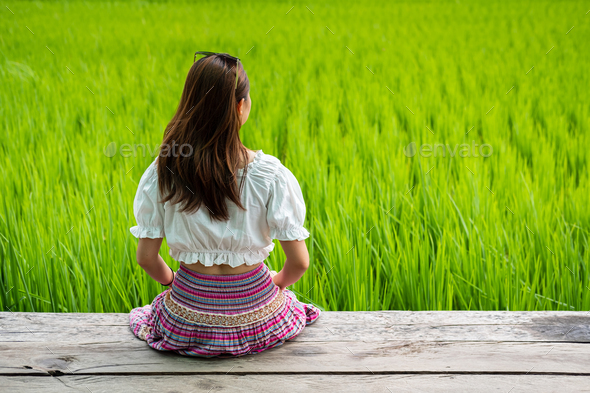 Young woman traveler sitting and relaxing with beautiful green paddy field - Stock Photo - Images