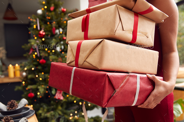 Close Up Of Woman Carrying Pile Of Christmas Presents Standing By Tree At Home - Stock Photo - Images