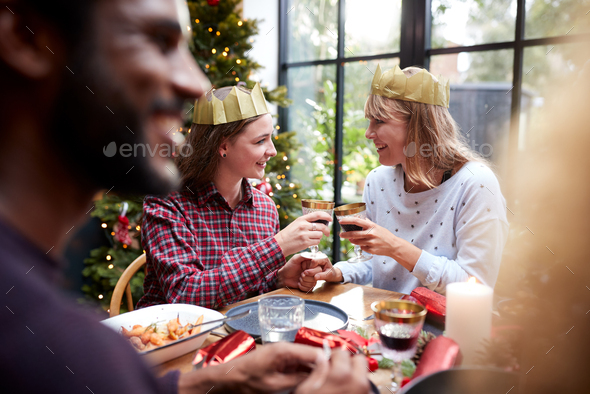 Gay Female Couple Sitting Around Table Making A Toast At Home And Eating Christmas Dinner - Stock Photo - Images