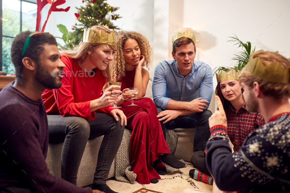Group Of Friends Playing Charades After Enjoying Christmas Dinner At Home - Stock Photo - Images