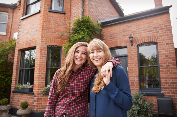 Portrait Of Excited Gay Female Couple Standing Outside New Home Together - Stock Photo - Images