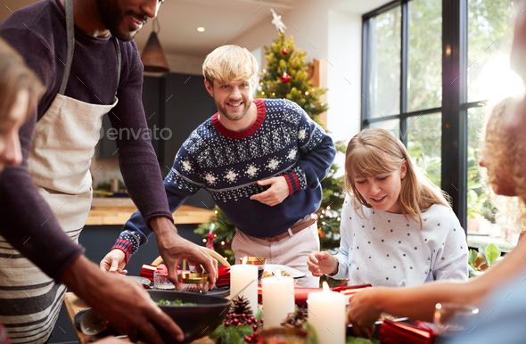 Group Of Friends Sitting Around Dining Table At Home As Christmas Dinner Is Served - Stock Photo - Images