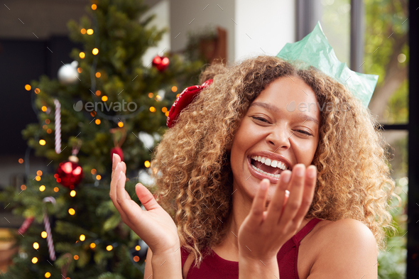 Portrait Of Smiling Woman Wearing Paper Hat Standing By Tree At Home - Stock Photo - Images