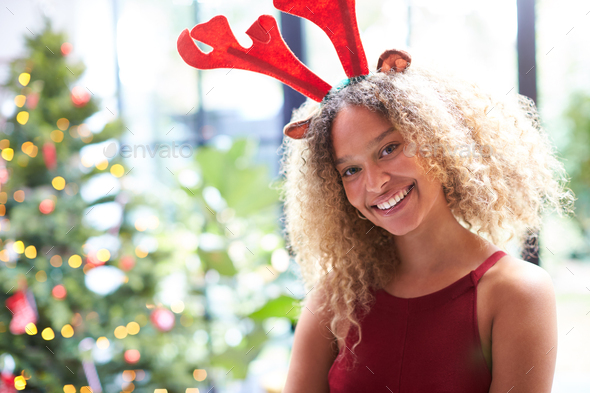Portrait Of Woman Wearing Fancy Dress Antlers Standing Next To Christmas Tree At Home - Stock Photo - Images