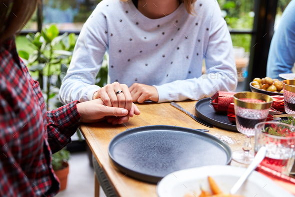 Close Up Of Gay Female Couple Sitting Around Table Holding Hands At Home And Eating Christmas Dinner - Stock Photo - Images