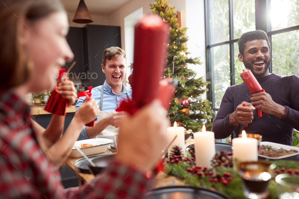 Group Of Friends Sitting Around Table At Home For Christmas Dinner Pulling Crackers - Stock Photo - Images