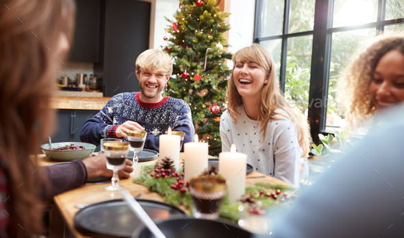 Group Of Friends Sitting Around Table At Home For Christmas Dinner Making A Toast - Stock Photo - Images
