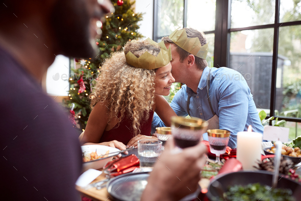 Couple Sitting Around Dining Table At Home For Christmas Dinner With Friends Whispering - Stock Photo - Images