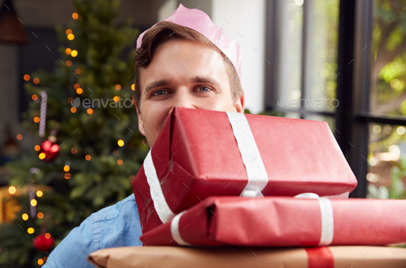 Portrait Of Man Wearing Paper Hat Carrying Pile Of Christmas Presents Standing By Tree At Home - Stock Photo - Images