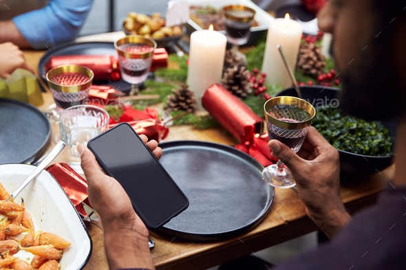 Group Of Friends Sitting Around Table At Home For Christmas Dinner Looking At Mobile Phone - Stock Photo - Images