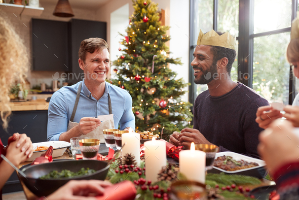 Group Of Friends Sitting Around Table At Home For Christmas Dinner Reading Jokes From Crackers - Stock Photo - Images