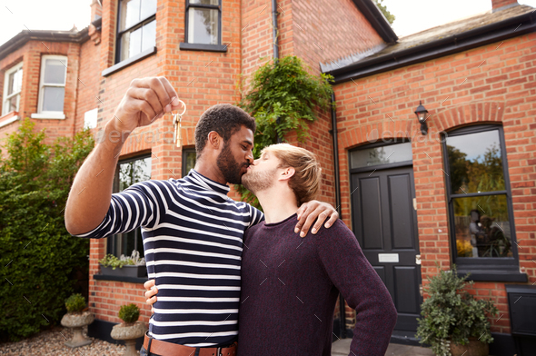 Gay Male Couple Standing Outside New Home On Moving Day Together Kissing And Holding Keys - Stock Photo - Images