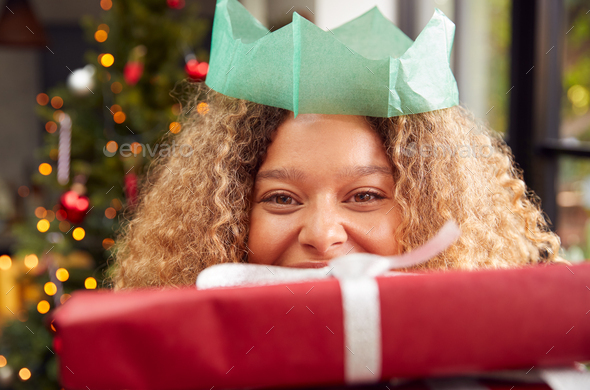 Portrait Of Woman Wearing Paper Hat Carrying Pile Of Christmas Presents Standing By Tree At Home - Stock Photo - Images