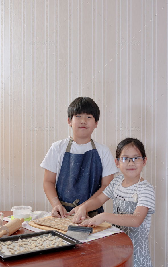 Brother and sister cooking by themself - Stock Photo - Images