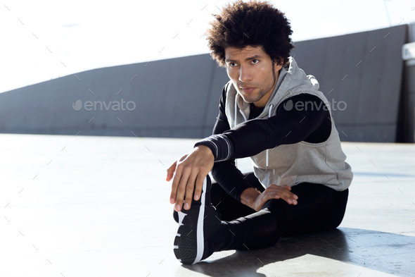 Fit and sporty young man doing stretching in city. - Stock Photo - Images