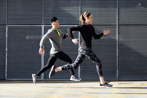 Fit and sporty couple running in the street. - Stock Photo - Images