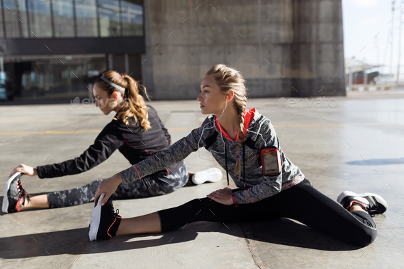Two fit and sporty young women doing stretching in city. - Stock Photo - Images